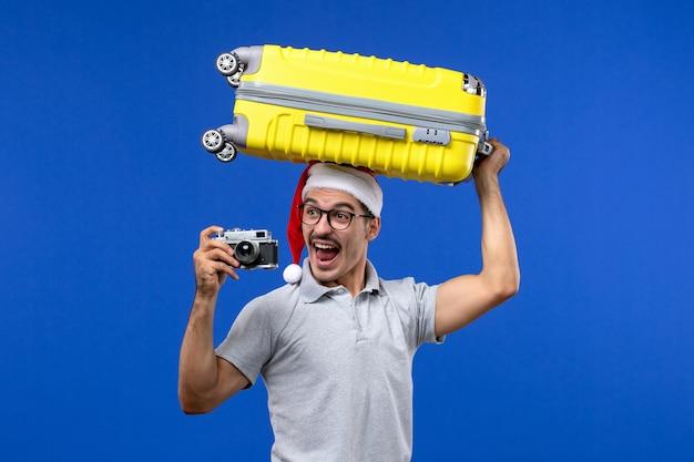 Jovem homem tirando fotos e segurando a bolsa em um avião de férias com parede azul