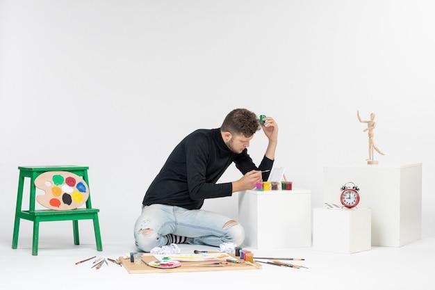 Jovem homem trabalhando com tintas na parede branca pintar arte colorida artista pintando desenho de foto de frente