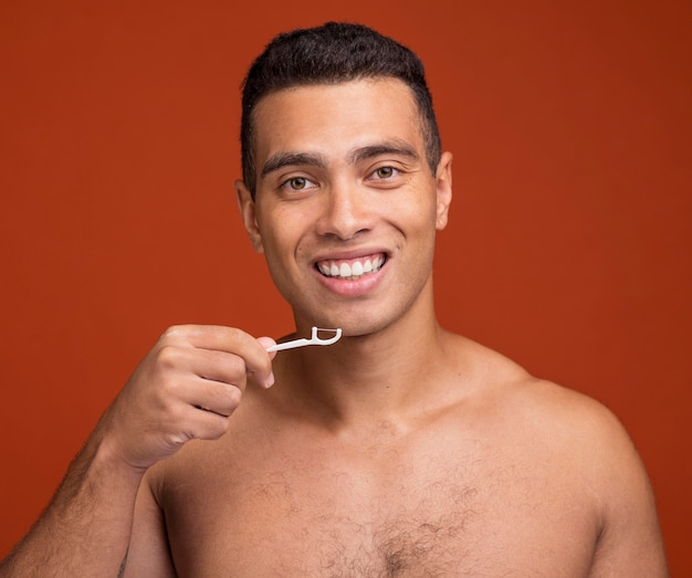 Jovem homem usando fio dental