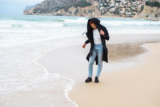 Jovem homem weared elegante está posando em uma praia