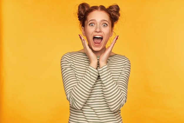 Jovem, horrorizada, mulher ruiva com dois pães. mostra o quanto ela tem medo do que vê. usando um suéter listrado e gritos isolados na parede amarela