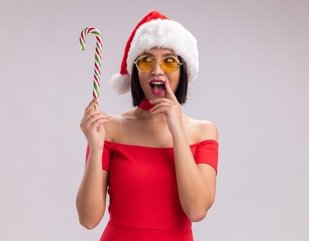 Jovem impressionada com chapéu de papai noel e óculos segurando e olhando para o bastão de doces de natal tocando o lábio isolado no fundo branco com espaço de cópia