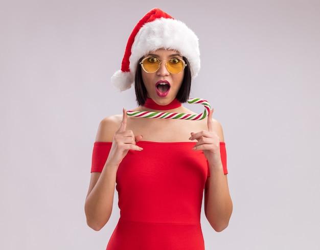 Jovem impressionada com chapéu de papai noel e óculos, segurando o bastão de doces de natal horizontalmente, olhando para a câmera, isolada no fundo branco com espaço de cópia
