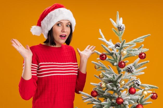 Jovem impressionada com chapéu de papai noel em pé perto de uma árvore de natal decorada, mostrando as mãos vazias isoladas em uma parede laranja