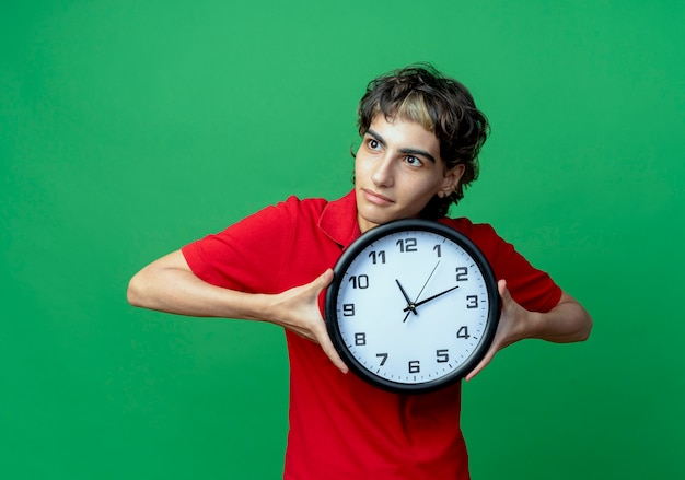 Jovem impressionada com um corte de cabelo de duende segurando um relógio olhando para o lado
