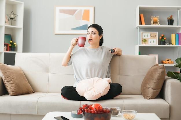 Jovem impressionada com um travesseiro segurando o controle remoto da tv e uma xícara de chá, sentada no sofá atrás da mesa de centro da sala de estar