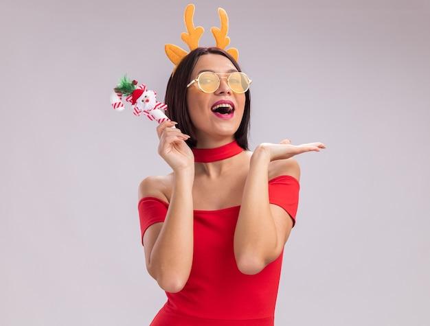 Jovem impressionada usando uma faixa de chifres de rena e óculos segurando um enfeite de bengala de doces de natal, olhando para a câmera, mostrando a mão vazia, isolada no fundo branco