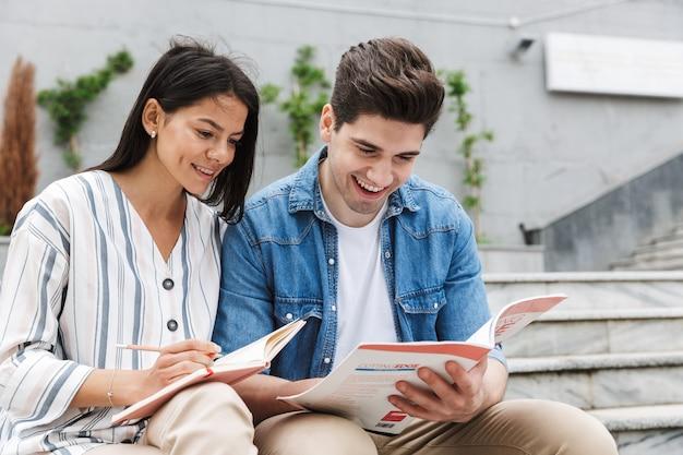 Jovem incrível casal amoroso colegas de alunos ao ar livre do lado de fora em etapas lendo livro escrevendo notas, estudando.