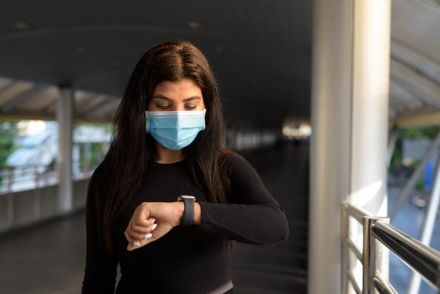 Jovem índia com máscara, verificando as horas em uma passarela na cidade