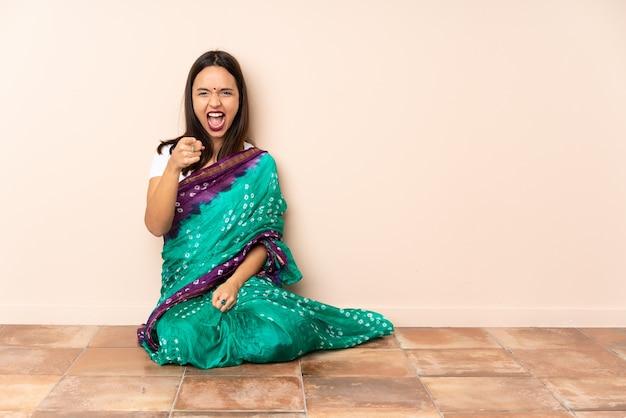 Jovem índia sentada no chão