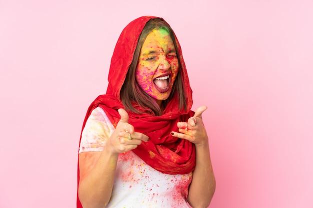 Jovem indiana com pós coloridos de holi no rosto, isolado na parede rosa, apontando para a frente e sorrindo