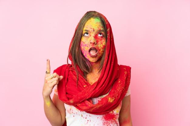 Jovem indiana com pós coloridos de holi no rosto isolado na parede rosa apontando para cima e surpreso