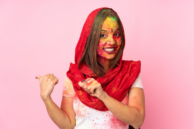 Jovem indiana com pós coloridos de holi no rosto, isolado na parede rosa, apontando para o lado para apresentar um produto