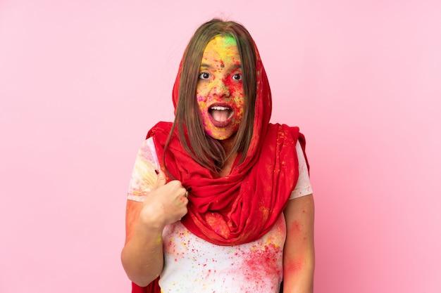 Jovem indiana com pós coloridos de holi no rosto isolado na parede rosa apontando para si mesmo