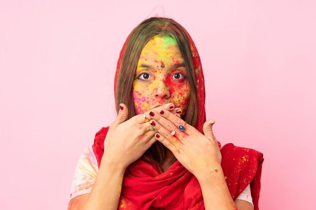 Jovem indiana com pós coloridos de holi no rosto isolado na parede rosa, cobrindo a boca com as mãos