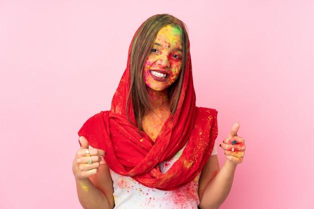 Jovem indiana com pós coloridos de holi no rosto isolado na parede rosa dando um polegar para cima gesto