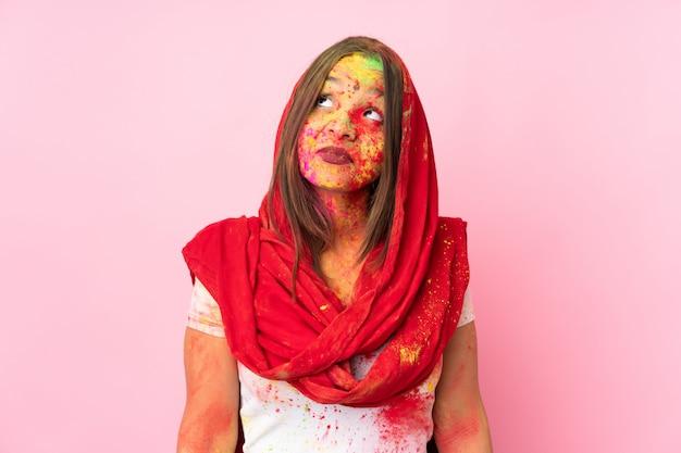 Jovem indiana com pós coloridos de holi no rosto isolado na parede rosa e olhando para cima