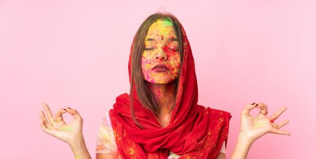 Jovem indiana com pós coloridos de holi no rosto isolado na parede rosa em pose de zen