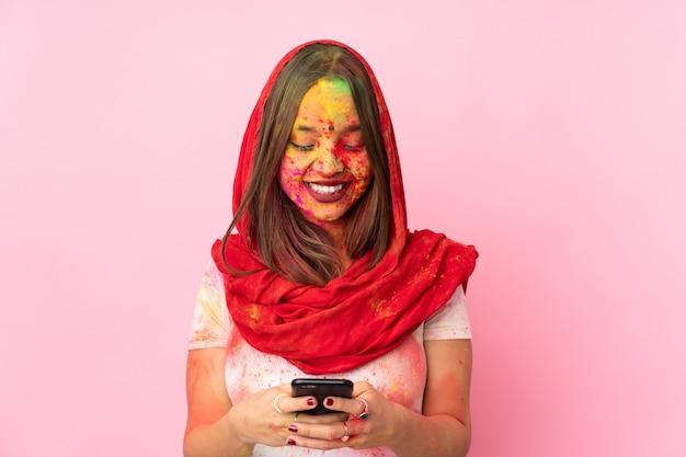 Jovem indiana com pós coloridos de holi no rosto isolado na parede rosa, enviando uma mensagem com o celular