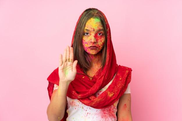 Jovem indiana com pós coloridos de holi no rosto isolado na parede rosa, fazendo o gesto de parada