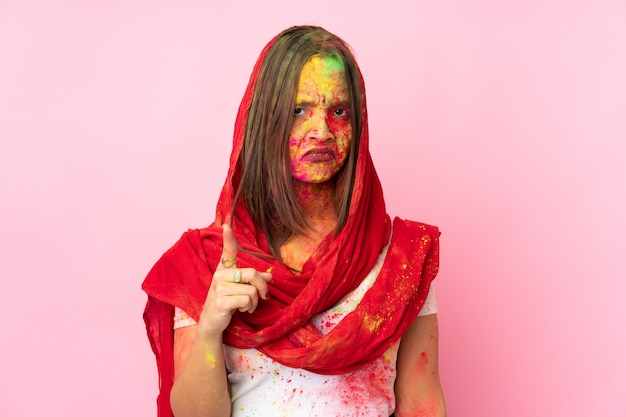 Jovem indiana com pós coloridos de holi no rosto isolado na parede rosa frustrada e apontando para a frente