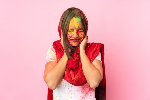 Jovem indiana com pós coloridos de holi no rosto isolado na parede rosa frustrado e cobrindo as orelhas