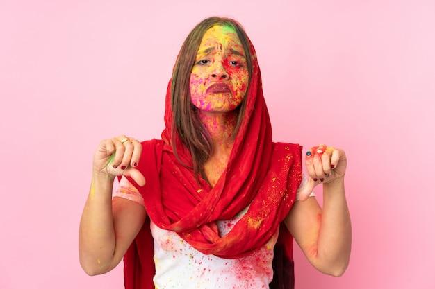 Jovem indiana com pós coloridos de holi no rosto isolado na parede rosa, mostrando o polegar para baixo com as duas mãos