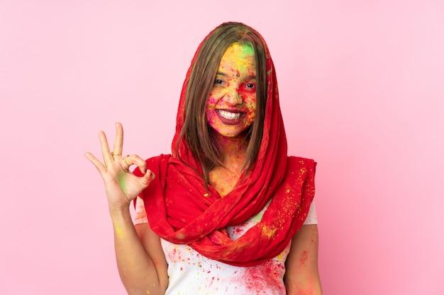 Jovem indiana com pós coloridos de holi no rosto isolado na parede rosa mostrando sinal de ok com os dedos
