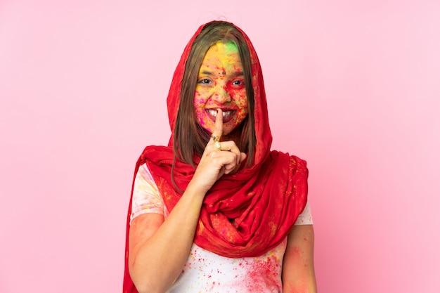 Jovem indiana com pós coloridos de holi no rosto isolado na parede rosa, mostrando um sinal de silêncio gesto colocando o dedo na boca