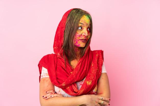 Jovem indiana com pós coloridos de holi no rosto isolado na parede rosa, olhando para o lado