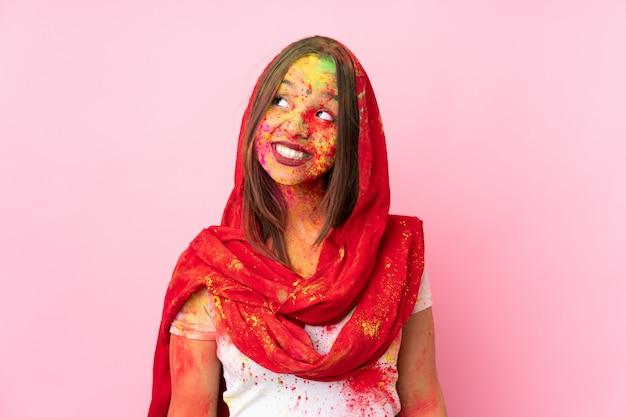 Jovem indiana com pós coloridos de holi no rosto isolado na parede rosa, pensando em uma idéia enquanto olha para cima