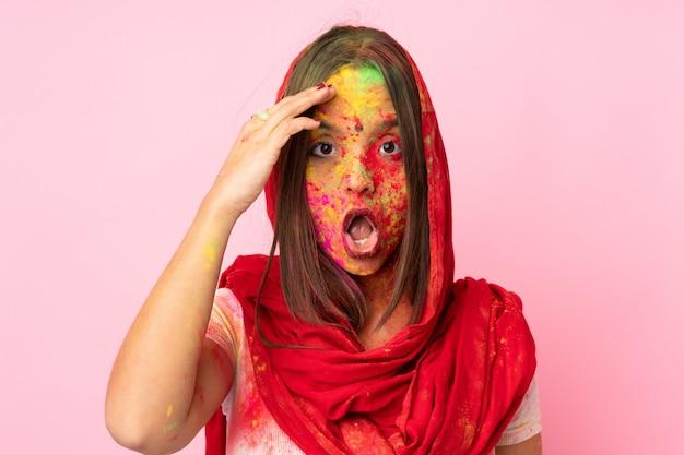 Jovem indiana com pós coloridos de holi no rosto, isolado na parede rosa, percebeu algo e pretendia a solução