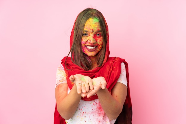 Jovem indiana com pós coloridos de holi no rosto isolado na parede rosa segurando copyspace imaginário na palma da mão para inserir um anúncio