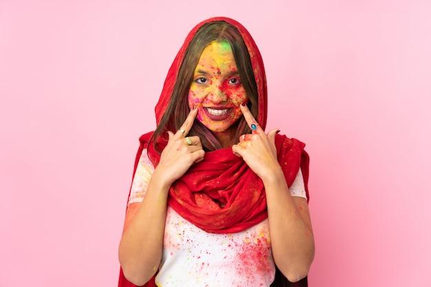 Jovem indiana com pós coloridos de holi no rosto isolado na parede rosa sorrindo com uma expressão feliz e agradável