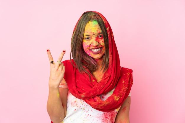 Jovem indiana com pós coloridos de holi no rosto isolado na parede rosa sorrindo e mostrando sinal de vitória