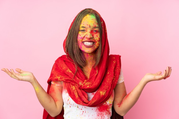 Jovem indiana com pós coloridos de holi no rosto isolado na parede rosa sorrindo muito
