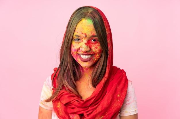 Jovem indiana com pós coloridos de holi no rosto isolado na parede rosa