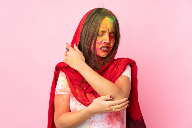 Jovem indiana com pós coloridos de holi no rosto na parede rosa com dor no cotovelo