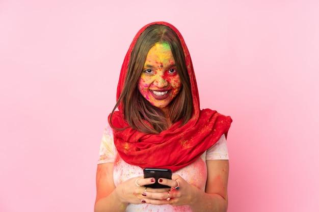 Jovem indiana com pós coloridos de holi no rosto na parede rosa, enviando uma mensagem com o celular
