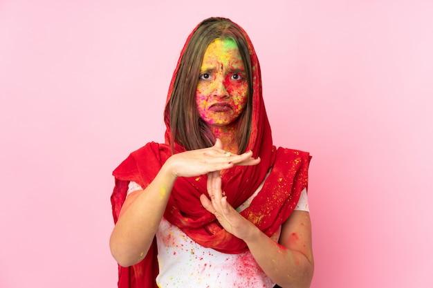 Jovem indiana com pós coloridos de holi no rosto na parede rosa fazendo gesto de tempo