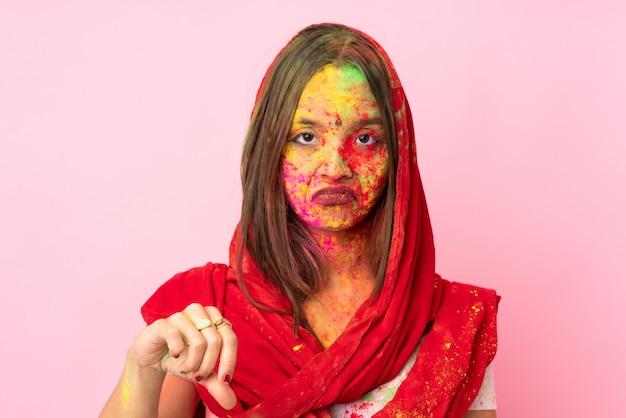 Jovem indiana com pós coloridos de holi no rosto na parede rosa, mostrando o polegar para baixo com expressão negativa
