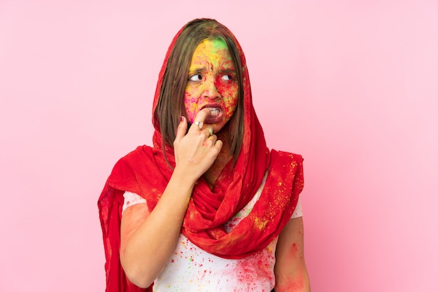 Jovem indiana com pós coloridos de holi no rosto na parede rosa nervosa e assustada