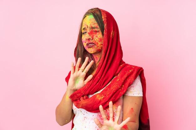 Jovem indiana com pós coloridos de holi no rosto na parede rosa nervosa esticando as mãos para a frente
