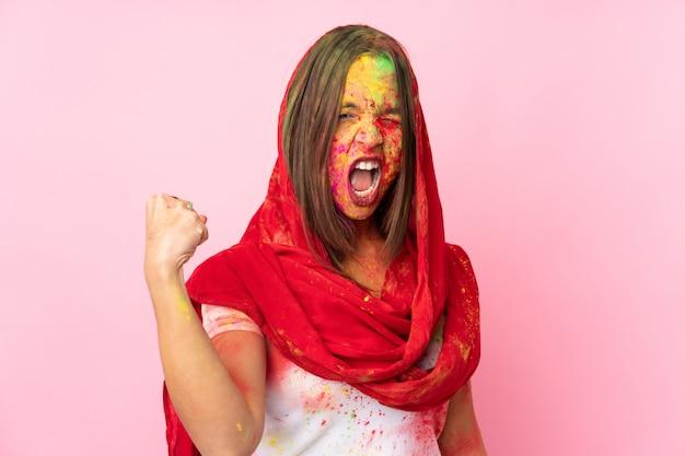 Jovem indiana com pós holi coloridos no rosto, isolado na parede rosa, fazendo um gesto forte