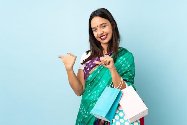 Jovem indiana com sacolas de compras apontando para o lado para apresentar um produto