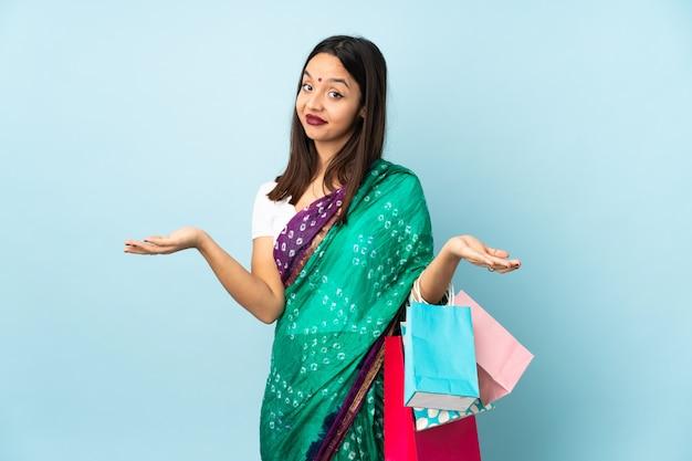 Jovem indiana com sacos de compras, tendo dúvidas
