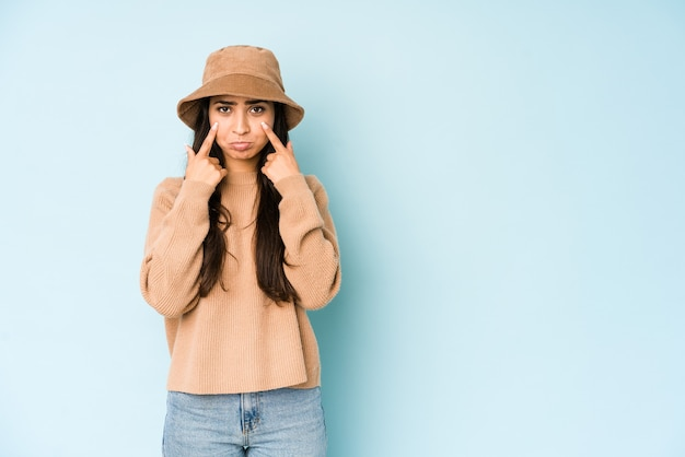 Jovem indiana com um chapéu isolado em um fundo azul, chorando, infeliz com algo, o conceito de agonia e confusão.