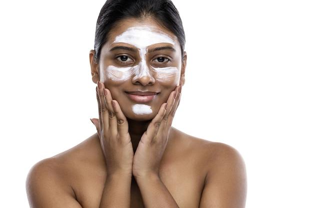 Jovem indiana com uma máscara de limpeza aplicada no rosto. isolado no branco.