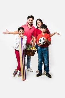 Jovem indiana família de quatro pessoas que vai para o piquenique - em pé sobre um fundo branco com cesta de frutas, tapete, futebol e bebidas. foco seletivo