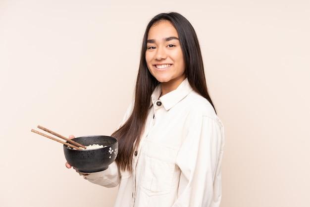 Jovem indiana isolada em um bege sorrindo muito enquanto segura uma tigela de macarrão com pauzinhos